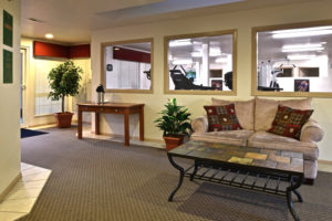 lobby with couch and coffee table, windows looking into fitness center